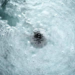 Black Water Color Changing Spellbound Woods Scented Bath Bomb by Tailored Soap in use close up