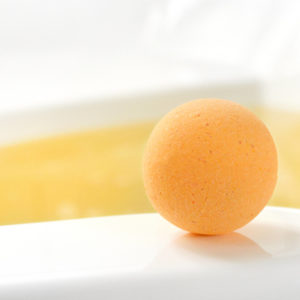 Orange Water Color Changing Plumeria Scented Bath Bomb by Tailored Soap in use